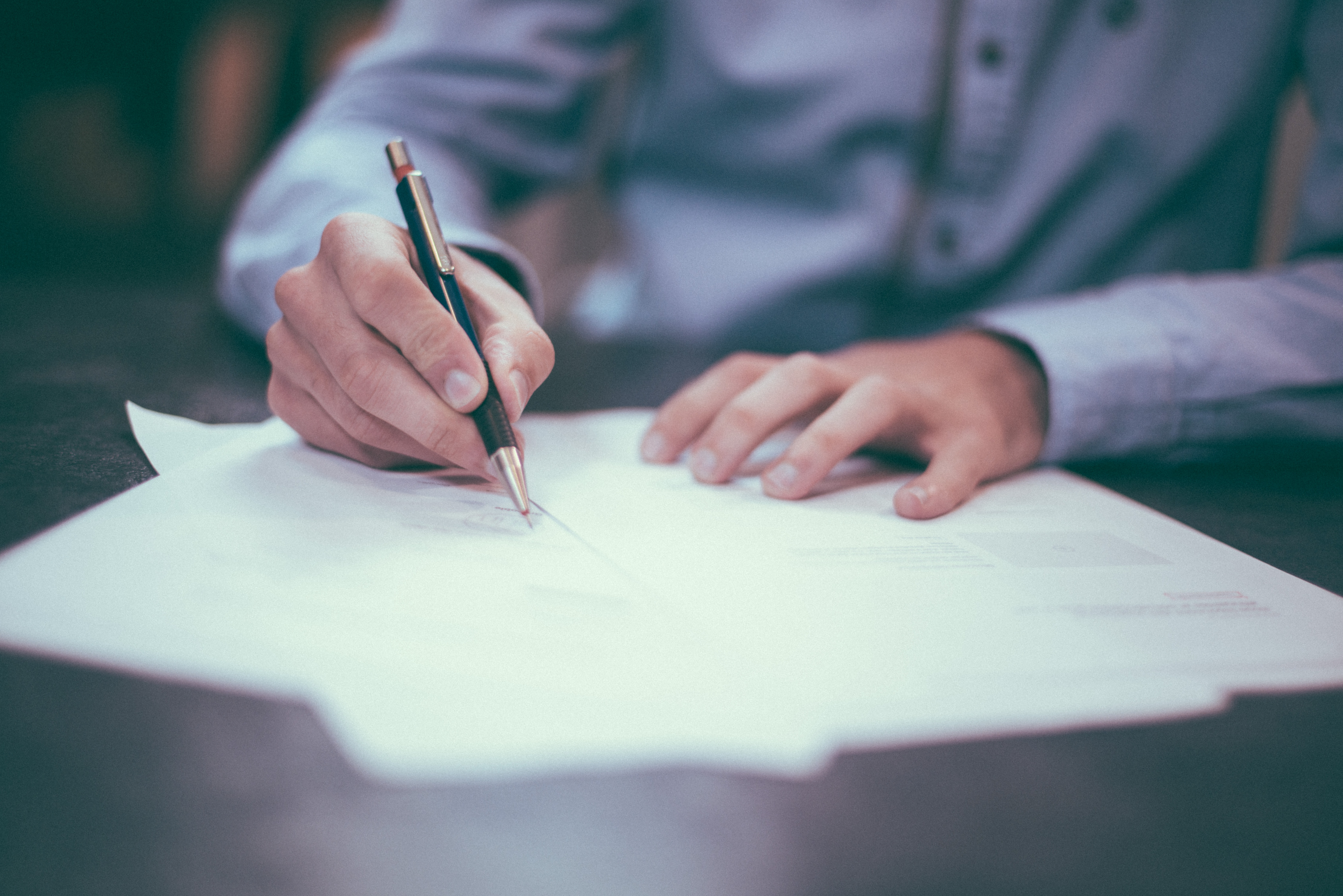Image of a man signing a written tenancy agreement