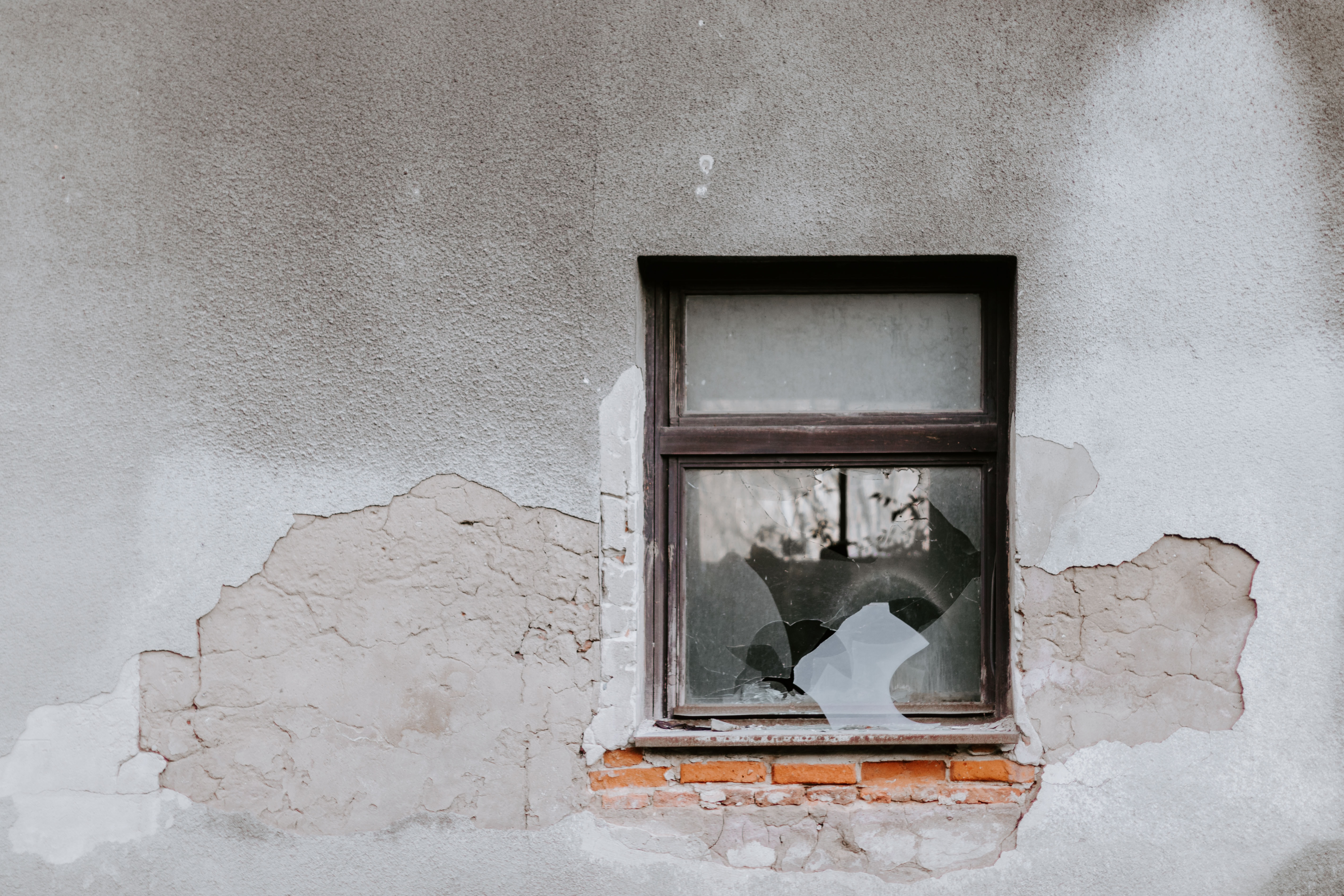 Picture of a broken window set in a cracked and broken wall