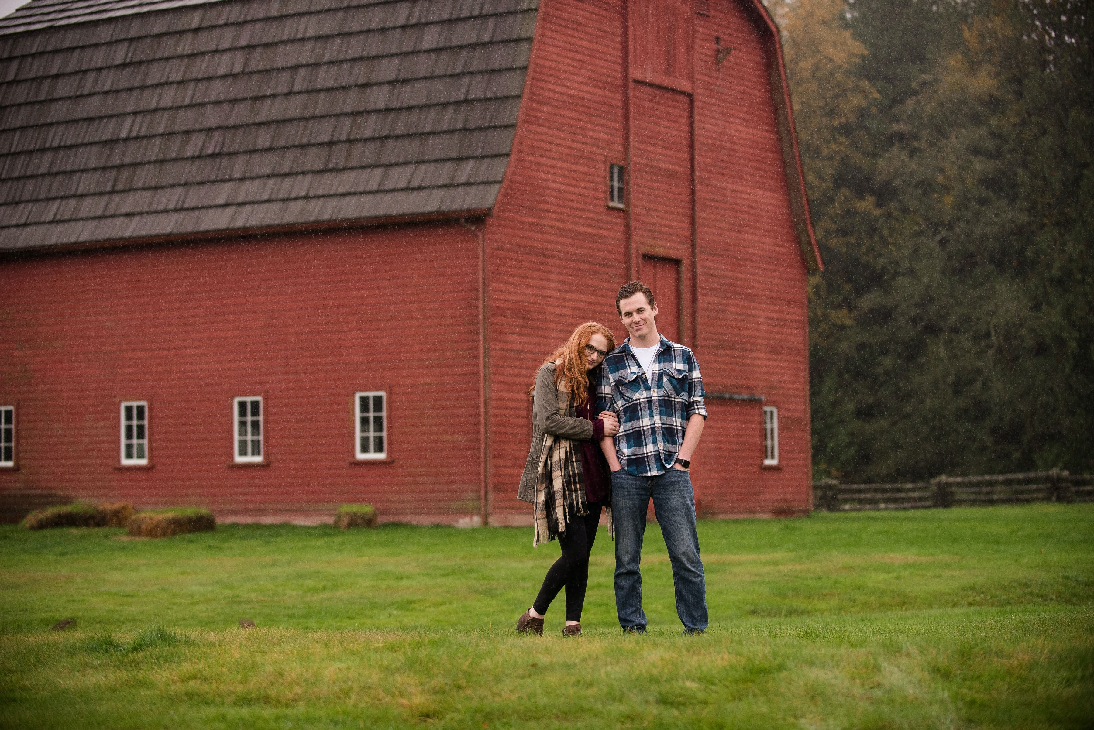 Picture of a couple stood next to a wooden barn