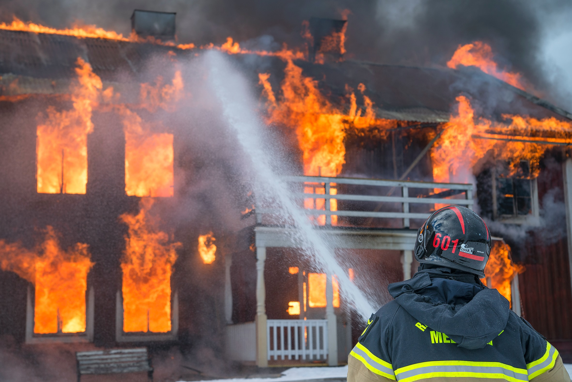 Picture of a fire-figher spraying water on a burning house
