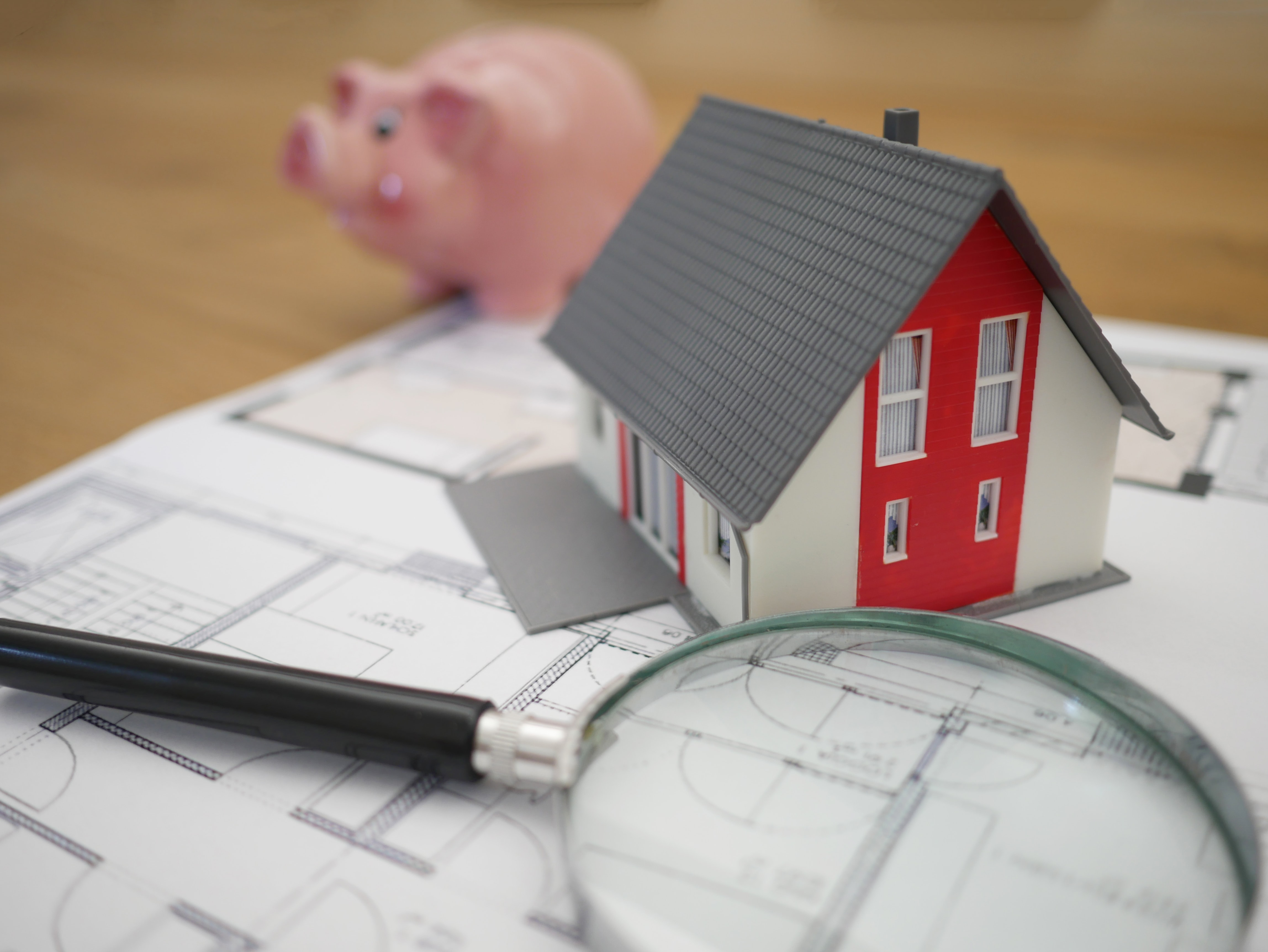 Picture of a magnifying glass, tiny house and a piggybank