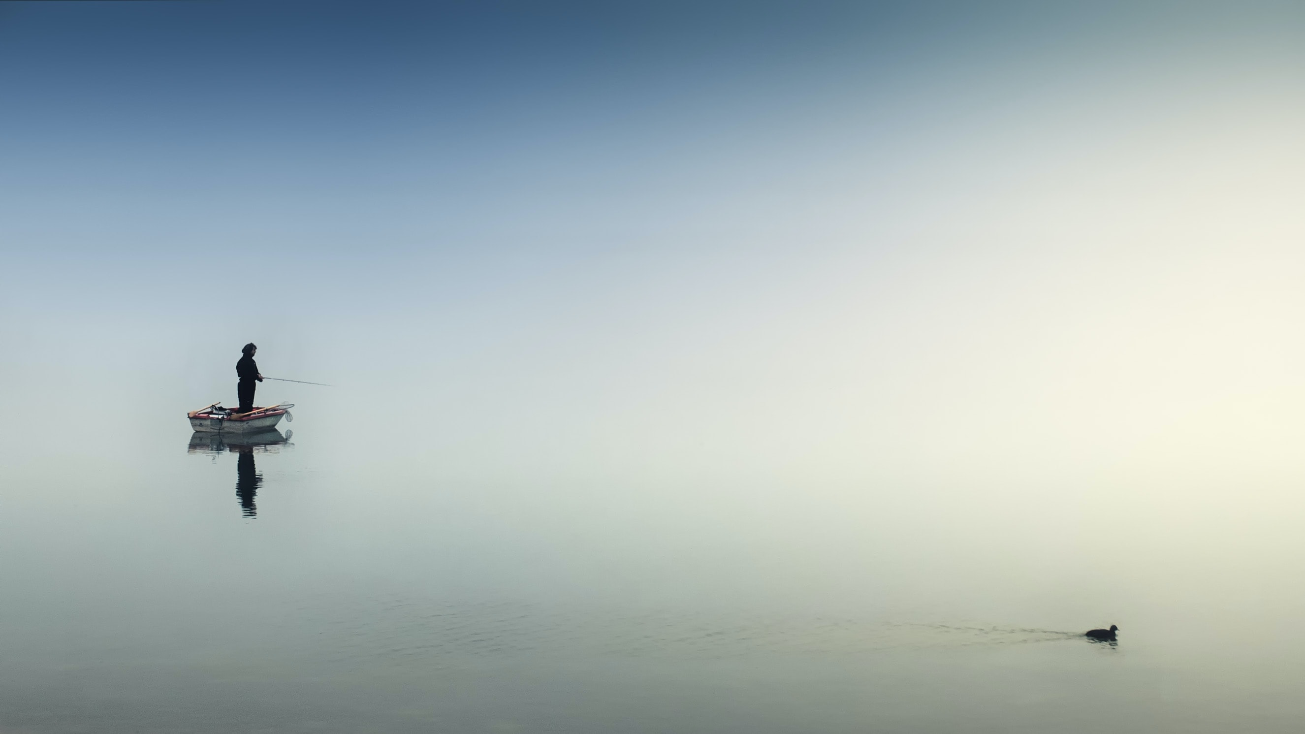 Picture of a man fishing on a quiet lake