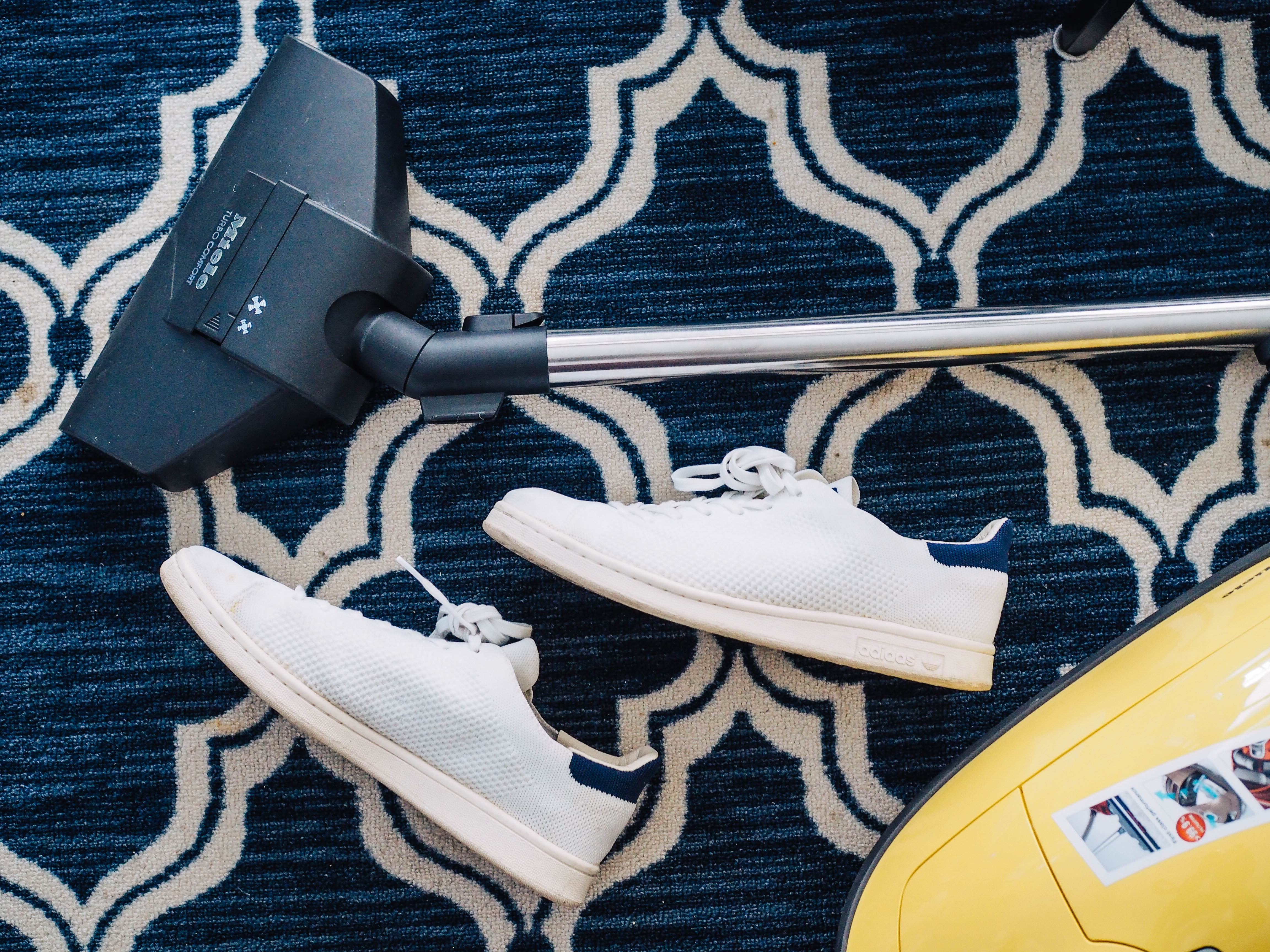 picture of a navy blue carpet vacuum cleaner and white trainers