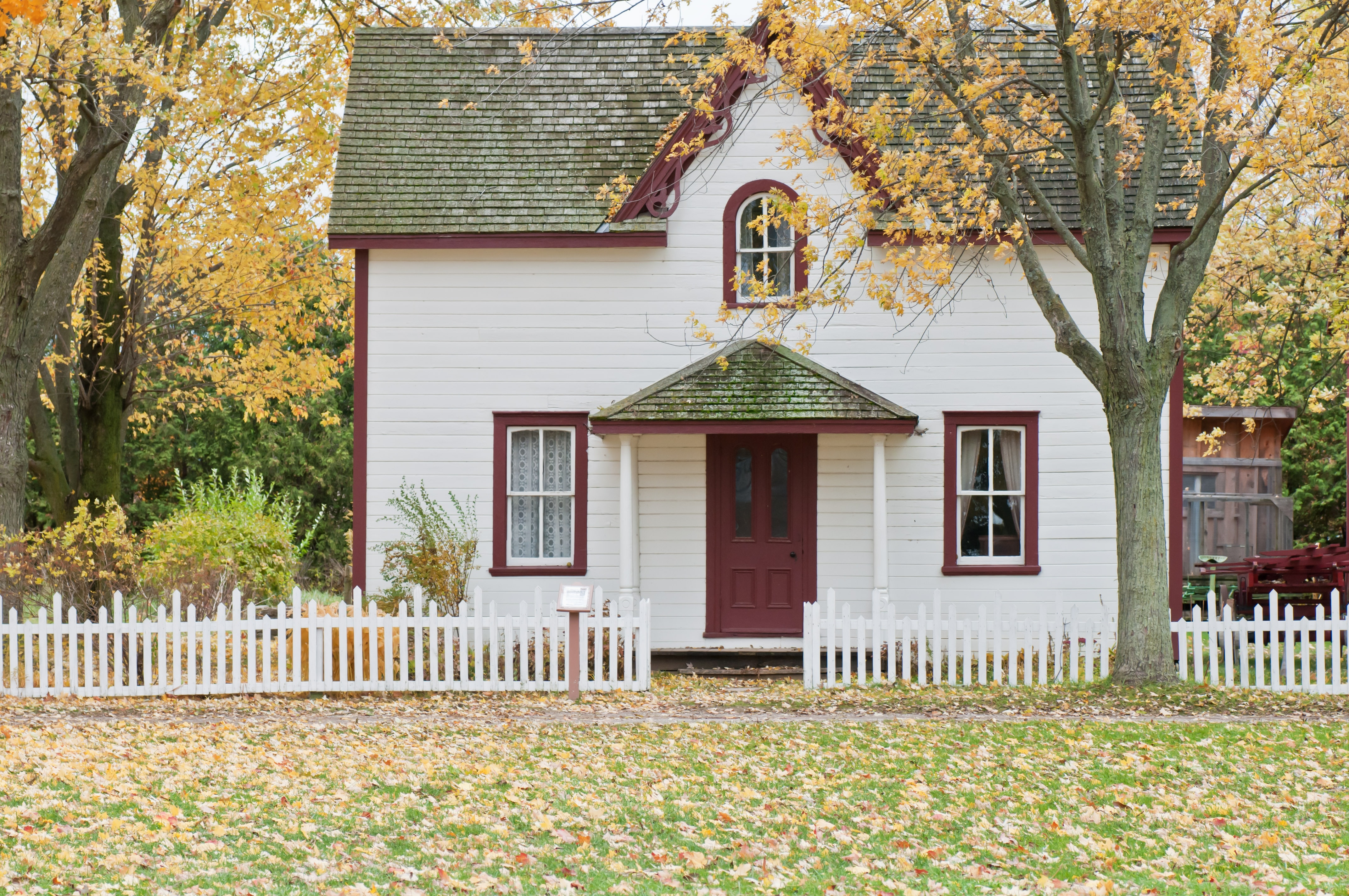 Picture of a white wooden house with a white picket fence