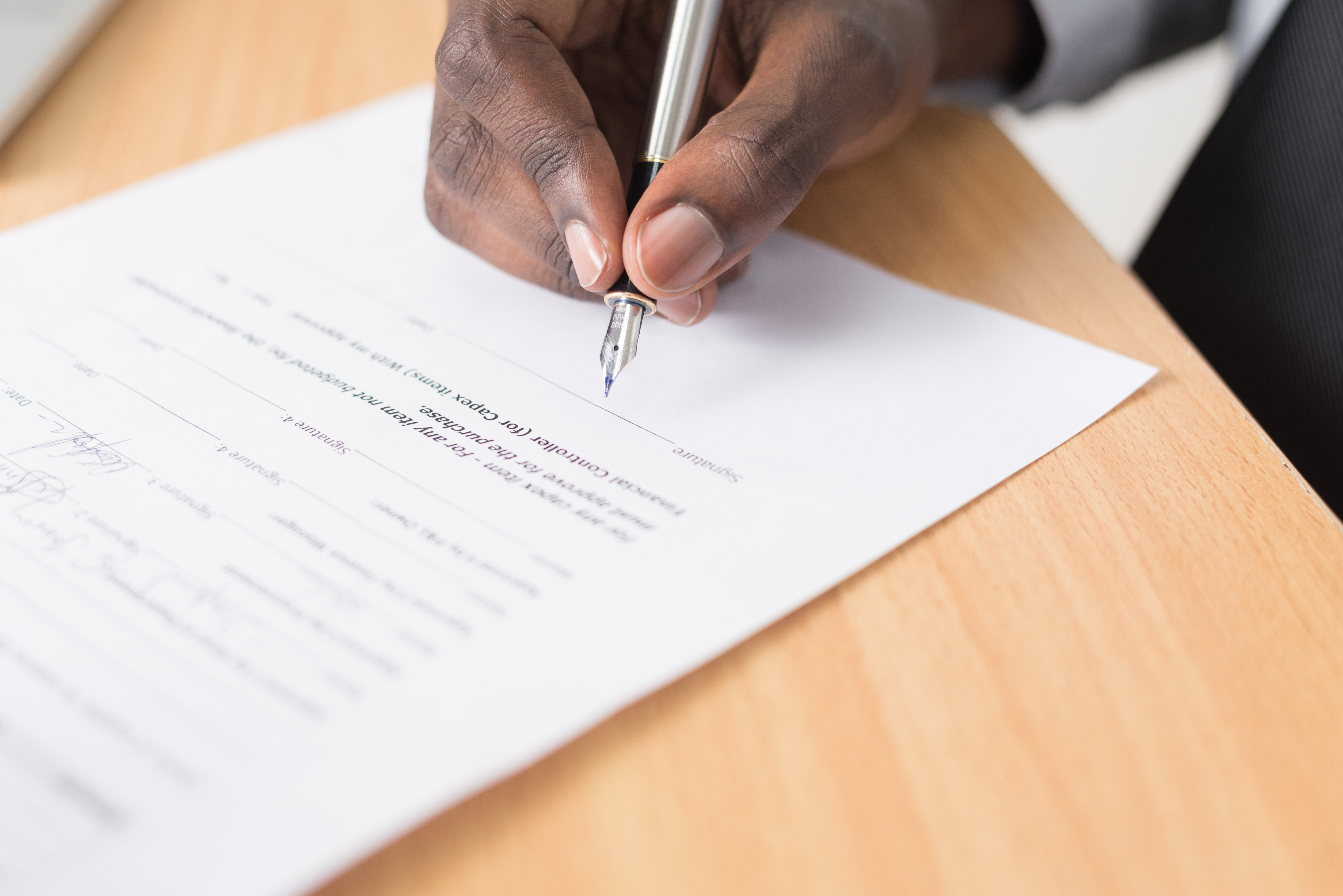 Picture of someone signing a contract with a fountain pen